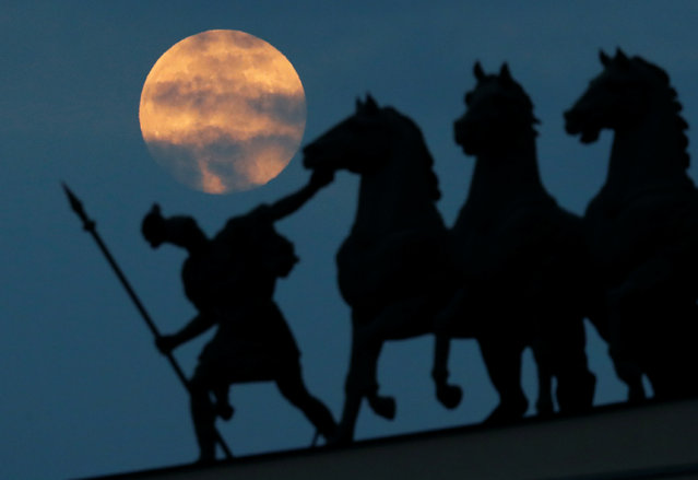 The pink supermoon rises behind the Chariot of Glory sculptural group in central Saint Petersburg, Russia on April 7, 2020. (Photo by Anton Vaganov/Reuters)