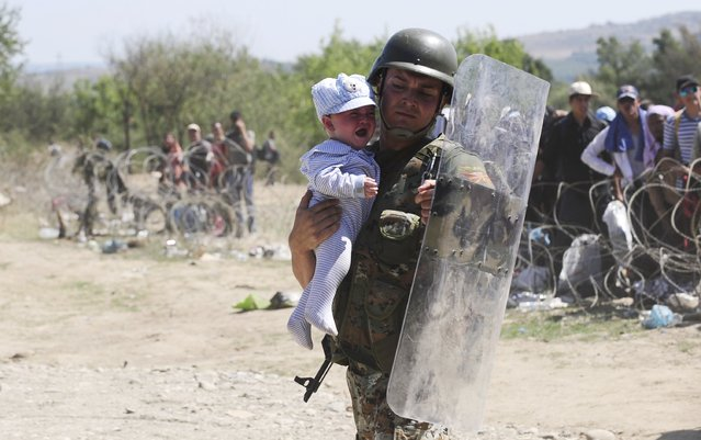 A policeman carries a baby to safety as migrants try to enter Macedonia near Gevgelija after crossing the border with Greece September 2, 2015. (Photo by Ognen Teofilovski/Reuters)