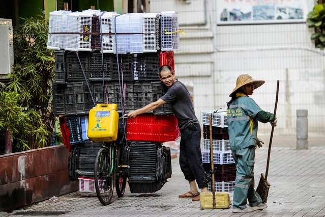A man moves a bicycle loaded with plastic boxes as he passes woman cleaning the street in Guangzhou, Guangdong province August 26, 2014. Any marked weakening in the labour market would raise alarm bells for China's leaders, who regard healthy employment levels as a top policy priority and an important condition for social stability. (Photo by Alex Lee/Reuters)