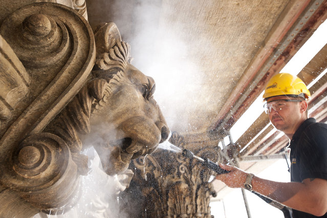 A man cleans the Prague National Theatre. (Photo by Caters News Agency)