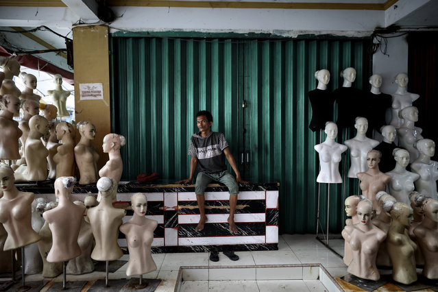In this April 10, 2020, photo, a worker sits near mannequins at a clothing market closed due to coronavirus outbreak in Jakarta, Indonesia. While its neighbors scrambled early this year to try to contain the spread of the new coronavirus, the government of the world's fourth most populous nation insisted that everything was fine. Only after the first cases were confirmed in March did President Joko Widodo acknowledge that his government was deliberately holding back information about the spread of the virus to prevent the public from panicking. The country now has the the highest death toll in Asia after China. (Photo by Dita Alangkara/AP Photo)