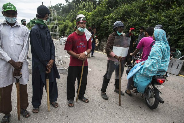 Protesters ride past a checkpoint guarded by their supporters at the entrance of an area under their control near the prime minister's house, on September 2, 2014. (Photo by Zohra Bensemra/Reuters)