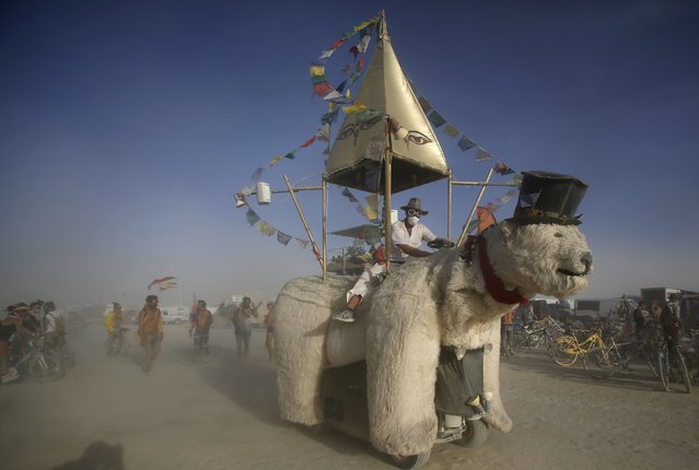 "A Mutant Vehicle made up like a polar bear drives through the dust during the Burning Man 2015 ""Carnival of Mirrors"" arts and music festival in the Black Rock Desert of Nevada, September 2, 2015. (Photo by Jim Urquhart/Reuters)"