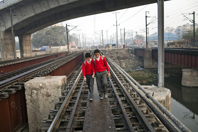 Boys walk to school over railway tracks close to the Nizamuddin Railway Station on February 06, 2012 in New Delhi, India. (Photo by Daniel Berehulak/Getty Images)