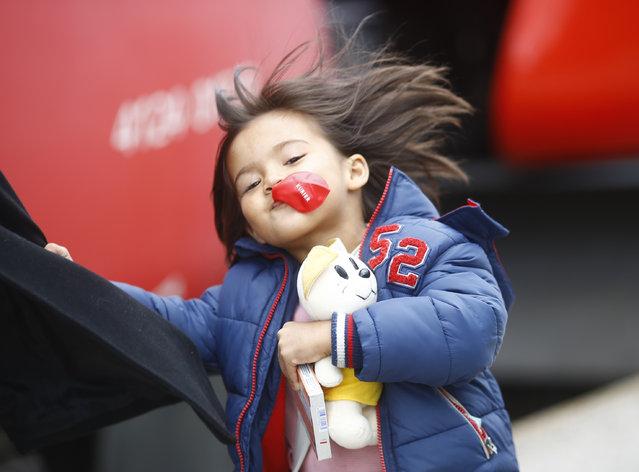 A young girl plays with a balloon as migrants board a train at the railway station in Nickelsdorf, Austria September 6, 2015. (Photo by Leonhard Foeger/Reuters)