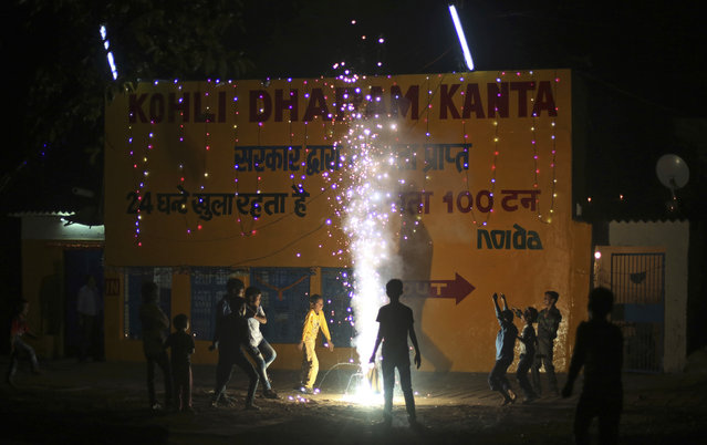 Indian children play with firecrackers to celebrate Diwali, the Hindu festival of lights, in New Delhi, India, Thursday, October 19, 2017. Worried especially by the impact on the health of children, the Supreme Court this year banned the sale of firecrackers in the Indian capital and neighboring areas to prevent a toxic haze after the Diwali nights that has residents hiding indoors. (Photo by Altaf Qadri/AP Photo)