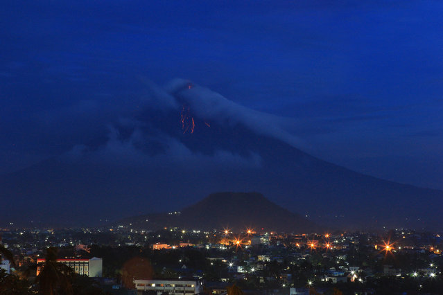 Lava cascades flow down the slope of restive Mayon Volcano as seen from Legazpi City, Albay province, Philippines, September 17, 2014. Tens of thousands of people living near the Philippines' most active volcano began to evacuate after increased activity prompted government scientists to warn of an imminent eruption. (Photo by Zalrian Z. Sayat/EPA)