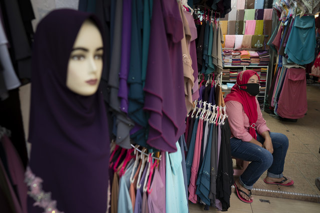 A shop vendor wearing a face mask to help curb the spread of the coronavirus waits for customer outside a shop in Kuala Lumpur, Malaysia, on Monday, May 11, 2020. Despite a sharp drop in infections, Malaysia's leader said restrictions to fight the coronavirus will be extended by four more weeks until June 9. The government has already let most businesses reopen with strict conditions to help revive a hard-hit economy. But mass gatherings are still barred, with schools, cinemas and houses of worship staying shut, group sports prohibited and interstate travel banned. (Photo by Vincent Thian/AP Photo)