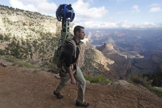 In this October 22, 2012, photo, Google product manager Ryan Falor walks with the Trekker during a demonstration for the media along the Bright Angel Trail at the South Rim of the Grand Canyon National Park in Arizona. The search engine giant is using the nearly 40-pound, backpack-sized camera unit to showcase the Grand Canyon's most popular hiking trails on the South Rim and other off-road sites. It's about 4 feet in height when set on the ground, and when worn, the camera system extends 2 feet above the operator's shoulders.  (Photo by Rick Bowmer/AP Photo)