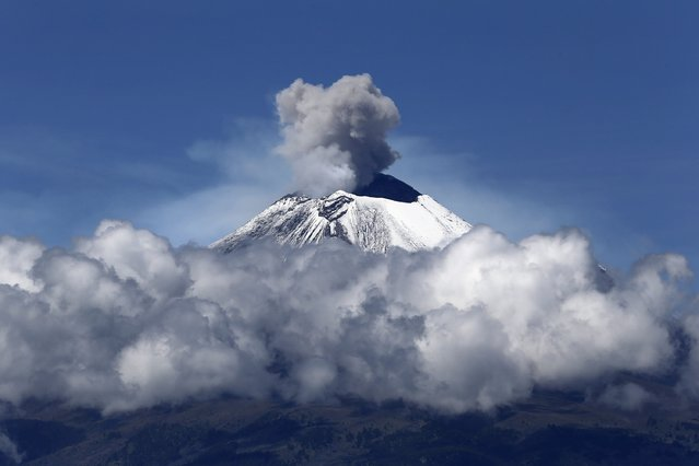 The snow-covered Popocatepetl volcano spews a cloud of steam high into the air as seen from Huejotzingo, on the outskirts of Mexico City September 25, 2014. (Photo by Tomas Bravo/AFP Photo)