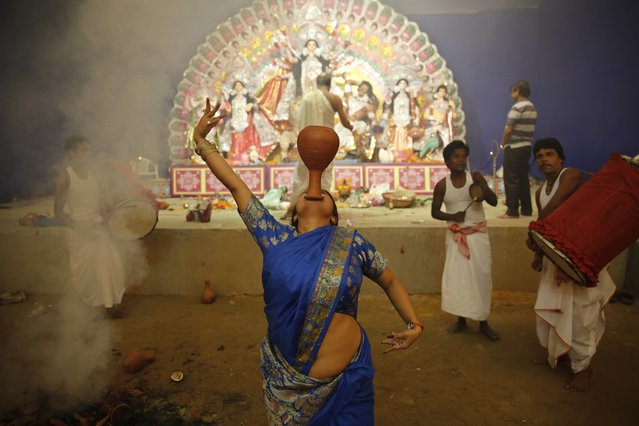 In this Wednesday, October 1, 2014 photo, a Hindu devotee performs a traditional Dhunuchi dance inside a temporary worship venue of goddess Durga during the Durga Puja festival in Allahabad, India. (Photo by Rajesh Kumar Singh/AP Photo)
