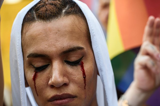 A LGBT member with make up on her face attends on August 21,2016 in Istanbul a demonstration for the murdering of a transgender activist Hande Kader, a 22-year-old transgender who was mutilated, burnt and murdered in Istanbul on last week. Nearly 200 militants of the transgender cause demonstrate in Istanbul to ask for justice after the murder of the transgender activist Hande Kader. It is the the second murder that horrified the Turkisk LGBT community after the killing, on August 4, 2016, of a Syrian refugee who was found dead with his body mutilated. (Photo by Ozan Kose/AFP Photo)