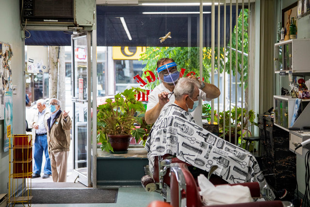 Joaquim Correia of College Barber Shop cuts a customer's hair while others wait outside for their appointment, as the provincial phase 2 of reopening from the coronavirus disease (COVID-19) restrictions begins in Toronto, Ontario, Canada on June 24, 2020. (Photo by Carlos Osorio/Reuters)