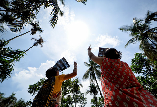 Two woman seen observing the solar eclipse from a terrace using an X ray plate in Kolkata, India on June 21, 2020. The partial solar eclipse in Kolkata will last for approximately three hours and 31 minutes. It began at 10:46 am local time and will end at 2:17 pm during this period around 67% of Sun will be covered by the shadow of Moon. (Photo by Avishek Das/SOPA Images/Rex Features/Shutterstock)