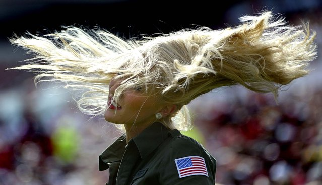 A Tampa Bay Buccaneers cheerleader, wear a military-inspired outfit as part of the NFL's Salute to Service program, flips her hair during a game between the Buccaneers and San Diego Chargers in Tampa, on November 11, 2012. (Photo by Phelan M. Ebenhack/Associated Press)