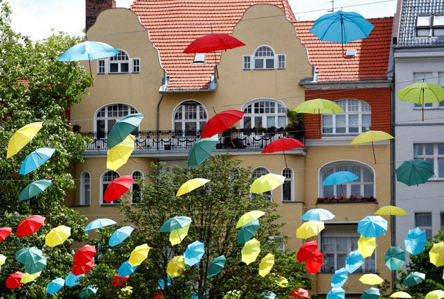 Coloured umbrellas are hanging on ropes over a square to advertise an upcoming wine festival at Berlin's Charlottenburg district in Berlin, Germany, June 30, 2020. (Photo by Fabrizio Bensch/Reuters)