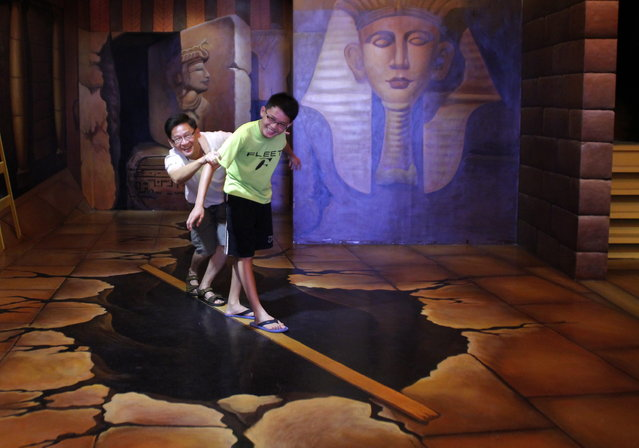 Visitors pose for a photo with a 3D artwork at Trick Art Museum in Shah Alam, outside Kuala Lumpur, Malaysia, Tuesday, Dec. 4, 2012. (AP Photo/Lai Seng Sin)