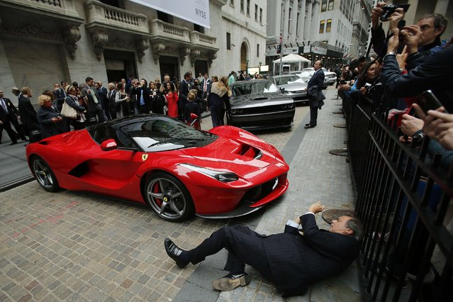 A man tries to take a picture of a Ferrari LaFerrari sports car parked at the entrance of the New York Stock Exchange in New York, October 13, 2014. Investors cautiously greeted the Wall Street debut on Monday of Fiat Chrysler Automobiles (FCA) , a move that shifts the carmaker's center of gravity away from Italy and caps a decade of canny dealmaking and tough restructuring by Chief Executive Sergio Marchionne. (Photo by Eduardo Munoz/Reuters)