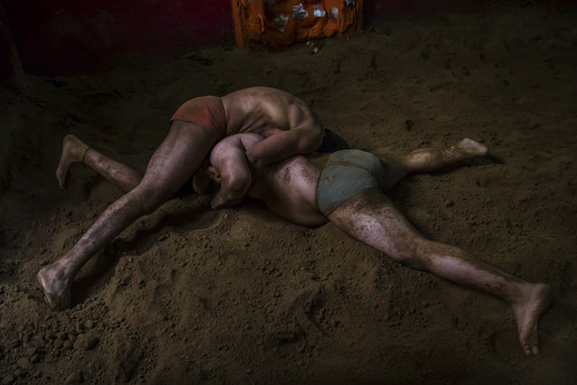 In this November 20, 2017 photo, Indian kushti wrestlers fight in the ring, during their daily training at an akhada, a kind of wrestling hostel at Sabzi Mandi, in New Delhi, India. (Photo by Dar Yasin/AP Photo)