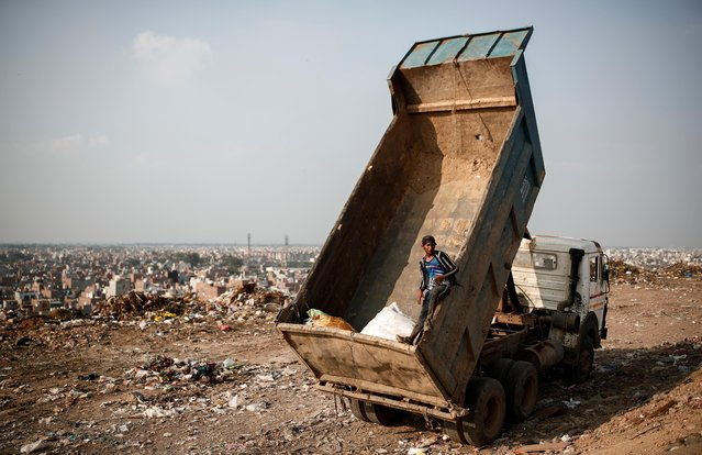 A waste collector stands inside a truck at a landfill site, during the coronavirus disease (COVID-19) outbreak, in New Delhi, India, July 9, 2020. (Photo by Adnan Abidi/Reuters)
