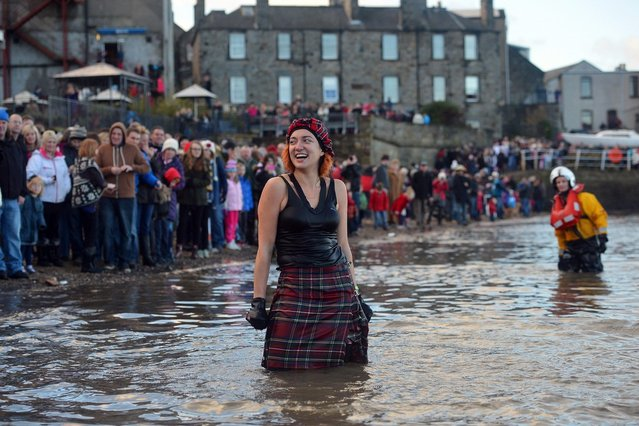 SOUTH QUEENSFERRY, SCOTLAND - JANUARY 01: A woman makes her way in the water wearing a kilt as she joined around 1,000 New Year swimmers, many in costume, braved freezing conditions in the River Forth in front of the Forth Rail Bridge during the annual Loony Dook Swim on January 1, 2013 in South Queensferry, Scotland. Thousands of people gathered last night to see in the New Year at Hogmanay celebrations in towns and cities across Scotland..  (Photo by Jeff J. Mitchell)