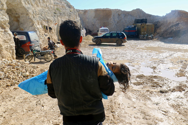 A man carries the body of a dead child, after what rescue workers described as a suspected gas attack in the town of Khan Sheikhoun in rebel-held Idlib, Syria, April 4, 2017. (Photo by Ammar Abdullah/Reuters)