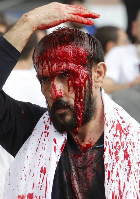 A Shi'ite Muslim man bleeds after tapping his forehead with a razor during a Muharram procession to mark Ashoura in Nabatieh town, southern Lebanon November 4, 2014. Ashoura, which falls on the 10th day of the Islamic month of Muharram, commemorates the death of Imam Hussein, grandson of Prophet Mohammad, who was killed in the seventh century battle of Kerbala. (Photo by Ali Hashisho/Reuters)
