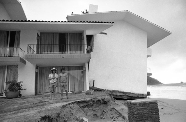 Hotel El Presidente, located in the beach resort town of Ixtapa, tilts precariously toward the Pacific Ocean after a tidal wave brought on by hurricane Madeline ate away the foundations. Two men in foreground survey the damage. Madeline came ashore near Ixtapa, Mexico on Friday, October 9, 1976, killing at least two persons and injuring nine others. (Photo by AP Photo/HEM)