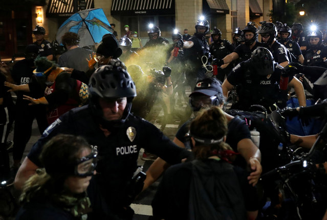 Policemen use pepper spray on demonstrators during a scuffle at a protest near the Charlotte Convention Center, the site of the Republican National Convention, in Charlotte, North Carolina, U.S. August 23, 2020. (Photo by Leah Millis/Reuters)