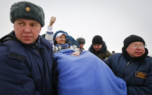 Ground personnel carry International Space Station (ISS) crew member Alexander Gerst of Germany (C) shortly after landing near the town of Arkalyk in northern Kazakhstan November 10, 2014. (Photo by Shamil Zhumatov/Reuters)
