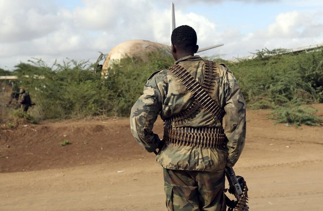 A Somalia government soldier stands guard to secure the site where a Tristar Air cargo plane crash-landed in Arbiska outside Somalia's capital Mogadishu, October 13, 2015. (Photo by Feisal Omar/Reuters)