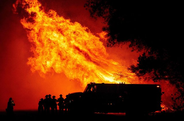 Butte county firefighters watch as flames tower over their truck during the Bear fire in Oroville, California on September 9, 2020. Dangerous dry winds whipped up California's record-breaking wildfires and ignited new blazes, as hundreds were evacuated by helicopter and tens of thousands were plunged into darkness by power outages across the western United States. (Photo by Josh Edelson/AFP Photo)