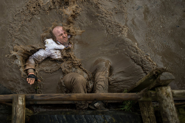 A competitor dressed in a white suit falls into muddy water as he negotiates an obstacle in the Tough Guy endurance event near Wolverhampton, central England, on February 4, 2018. The Tough Guy event challenges thousands of competitors to run a gruelling course whilst negotiating over 200 obstacles including water, fire, and tunnels. (Photo by Oli Scarff/AFP Photo)