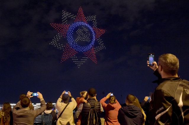 People watch a drone light show dedicated to the 75th anniversary of the end of World War Two in the center of Saint Petersburg on September 3, 2020. (Photo by Olga Maltseva/AFP Photo)