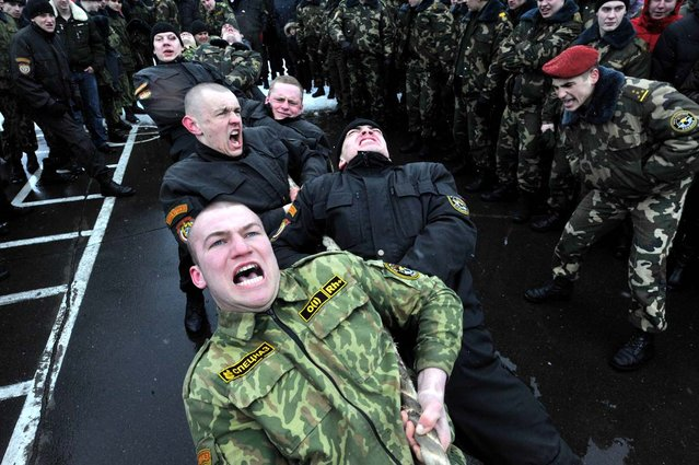 Belarus soldiers from an Interior Ministry special unit compete in a tug-of-war during a military show marking Maslenitsa holiday on the outskirts of Minsk on March 3, 2013. Maslenitsa is an medieval pagan festival that celebrates the end of winter and the start of spring. (Photo by Victor Drachev/AFP Photo)
