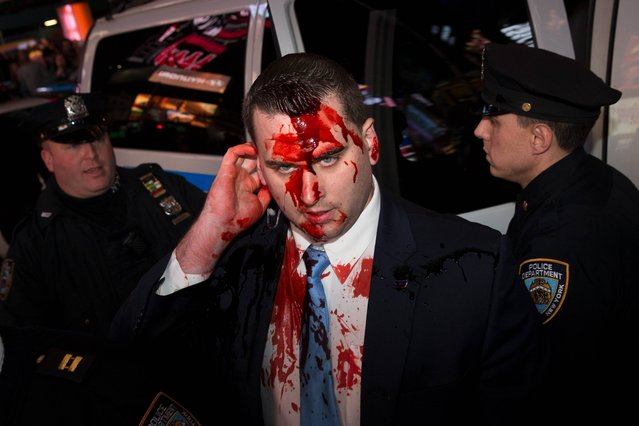 Imitation blood runs down the face of a police officer has he was splattered by a protestor in Times Square after the announcement of the grand jury decision not to indict police officer Darren Wilson in the fatal shooting of Michael Brown, an unarmed 18-year-old black man, Monday, November 24, 2014, in New York. (Photo by John Minchillo/AP Photo)