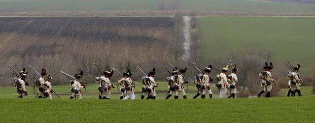 Historical re-enactment enthusiasts dressed as soldiers march near the southern Moravian village of Herspice November 28, 2014. (Photo by David W. Cerny/Reuters)