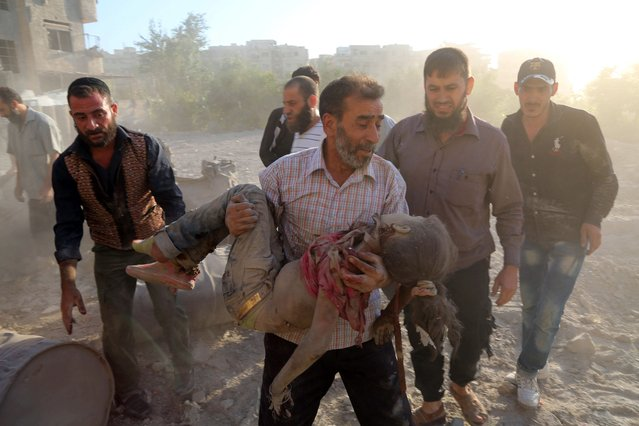 A Syrian man carries the body of a girl following a reported airstrike on Kafr Batna, in the rebel-held Eastern Ghouta area, on the outskirts of the capital Damascus, on September 30, 2016. Air raids on several rebel-held towns in the Eastern Ghouta region killed at least 17 people including eight children, the Syrian Observatory for Human Rights monitor said. (Photo by Amer Almohibany/AFP Photo)