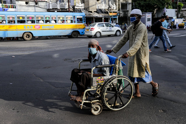 A man pushes a disabled man on wheelchair, both wearing face masks to prevent spreading coronavirus in Kolkata, India, Monday, October 5, 2020. India, the second worst-affected nation in the world after the United States, is witnessing a sustained decline in new coronavirus infections and active virus cases have remained below the million mark for 14 consecutive days. (Photo by Bikas Das/AP Photo)