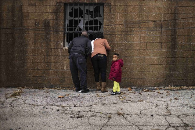 A family looks through the destroyed windows of the Flood Christian Church, which was set a flame during recent unrest in Ferguson, Missouri November 30, 2014. (Photo by Adrees Latif/Reuters)