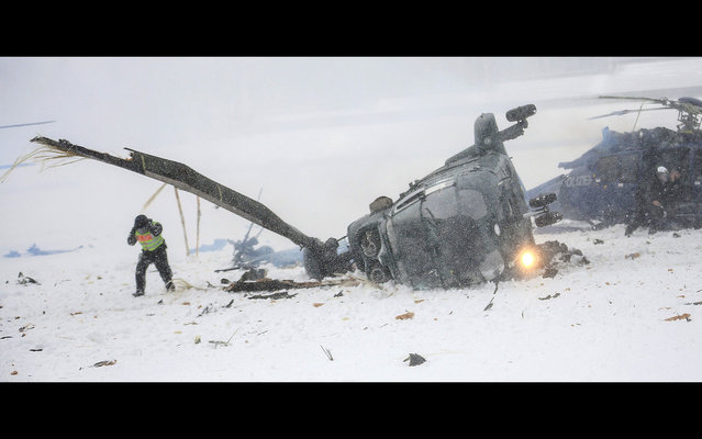 Police officers work at the scene where two police helicopters crashed near the Olympic stadium in Berlin, on March 21, 2013. The helicopters crashed as they were landing after a training exercise. (Photo by Hannibal Hanschke/AP Photo)