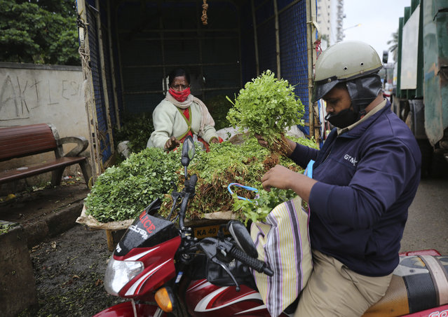A vegetable vendor wearing face mask as a precaution against the coronavirus sells vegetables to a policeman in Bengaluru, India, Sunday, October 11, 2020. India's confirmed coronavirus toll crossed 7 million on Sunday with a number of new cases dipping in recent weeks, even as health experts warn of mask and distancing fatigue setting in. (Photo by Aijaz Rahi/AP Photo)