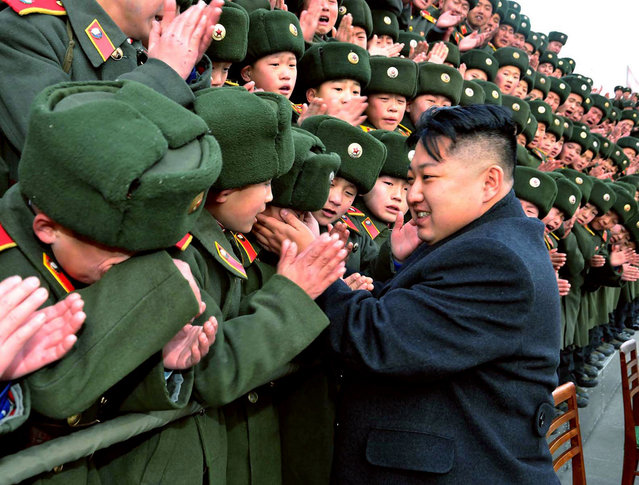 This picture taken by North Korea's official Korean Central News Agency shows North Korean leader Kim Jong Un greeting students during a visit to the Mangyongdae Revolutionary School on January 23, 2012. (Photo by AFP Photo/KNS)