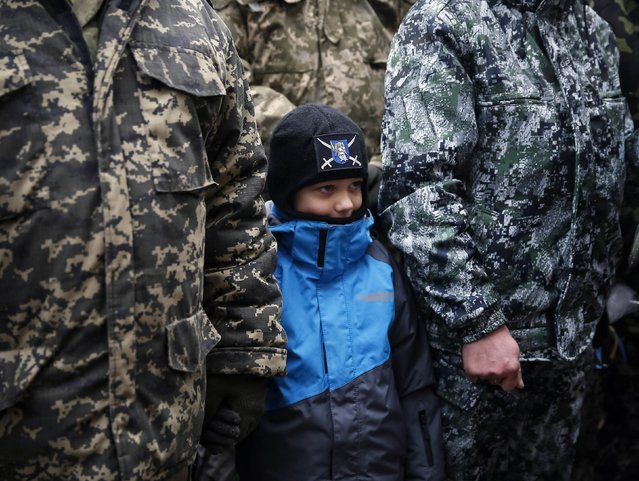 "A serviceman of ""Kiev 12"" military defence battalion holds a hand of his son as he attends a welcoming ceremony in central Ukrainian capital Kiev December 6, 2014. (Photo by Gleb Garanich/Reuters)"