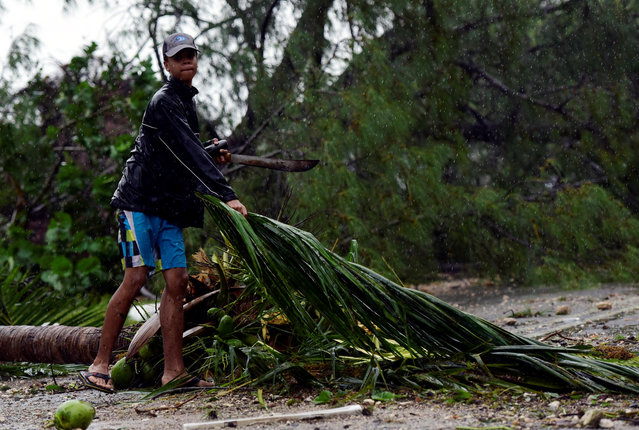 A boy helps to clear storm debris from Eastern Road in the aftermath of Hurricane Matthew striking Nassau, Bahamas October 6, 2016. (Photo by Dante Carrer/Reuters)
