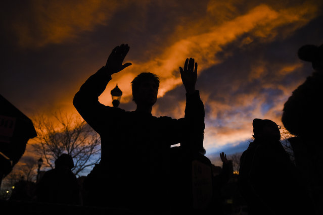 """Gus Griffin raises his hands during a """"hands up, don't shoot"""" chant, Tuesday, November 25, 2014 during a protest march in downtown Colorado Springs, Colo. against the grand jury decision to not indict Ferguson, Mo. police officer Darren Wilson for shooting unarmed 18-year-old Michael Brown. (Michael Ciaglo/AP Photo/The Gazette)"""