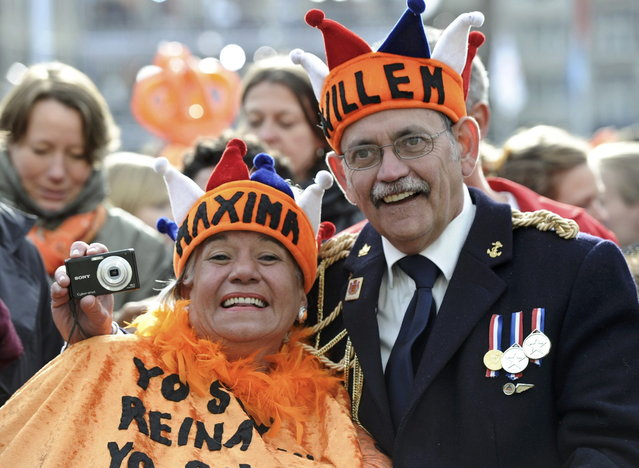 A couple waits for Queen Beatrix's abdication ceremony outside the Royal Palace in Amsterdam April 30, 2013. The Netherlands is celebrating Queen's Day on Tuesday, which will also mark the abdication of Queen Beatrix and the investiture of her eldest son Willem-Alexander. (Photo by Paul Vreeker/Reuters)