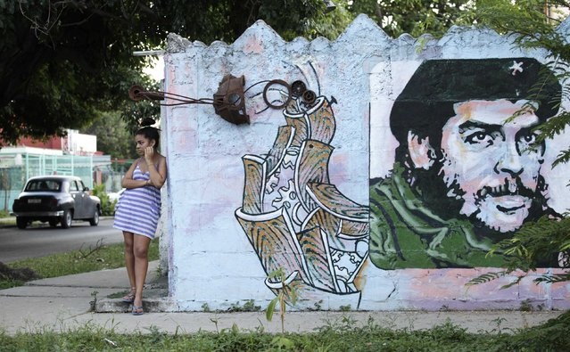 "A young woman stands near a mural of late revolutionary hero Ernesto ""Che"" Guevara in Havana December 22, 2014. From bus drivers to bartenders and ballet dancers, many Cubans are already imagining a more prosperous future after the United States said it will put an end to 50 years of conflict with the communist-run island. (Photo by Enrique De La Osa/Reuters)"