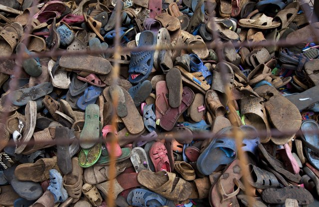 In this photo taken Monday, April 29, 2013, a pile of discarded flip-flops sits in a crate ready to be washed, sorted, and carved into toy animals, at the Ocean Sole flip-flop recycling company in Nairobi, Kenya. The company is cleaning the East African country's beaches of used, washed-up flip-flops and the dirty pieces of rubber that were once cruising the Indian Ocean's currents are now being turned into colorful handmade giraffes, elephants and other toy animals. (Photo by Ben Curtis/AP Photo)