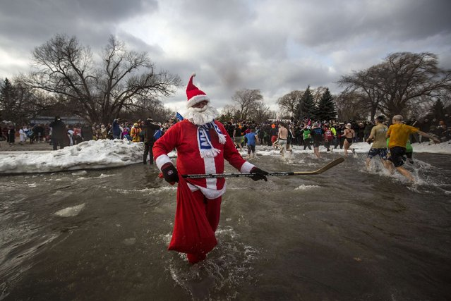 A man dressed as Santa Claus holds a hockey stick while taking part in Courage Polar Bear Dip at Coronation Park in Oakville, January 1, 2015. (Photo by Mark Blinch/Reuters)